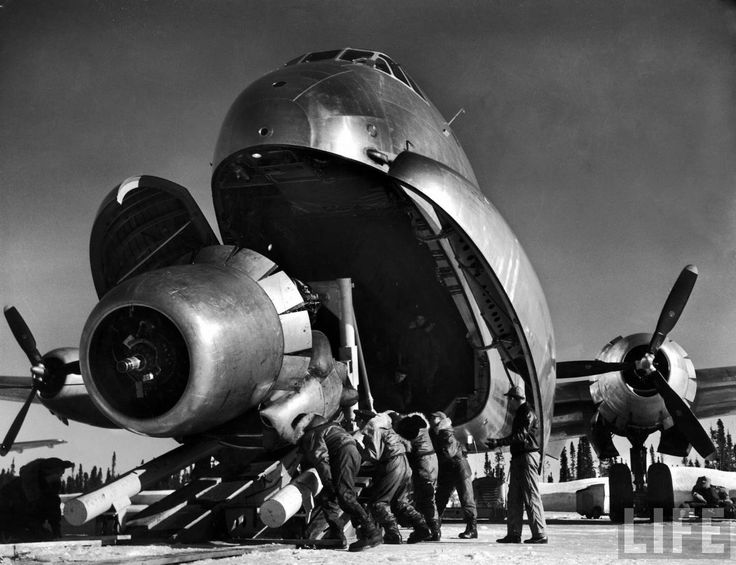 Margaret Bourke-White     Crewmen unloading huge B-50 bomber plane engine used as a spare from the belly of a C-124 Cargo plane upon arrival at Strategic Air Command's advance base.  Greenland   April 1951