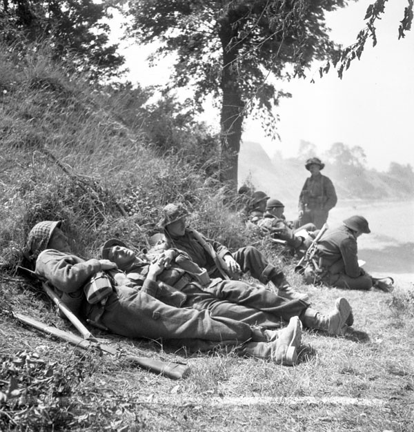 Infantrymen of The Highland Light Infantry of Canada resting alongside the Orne River en route to Caen, France, 18 July 1944.