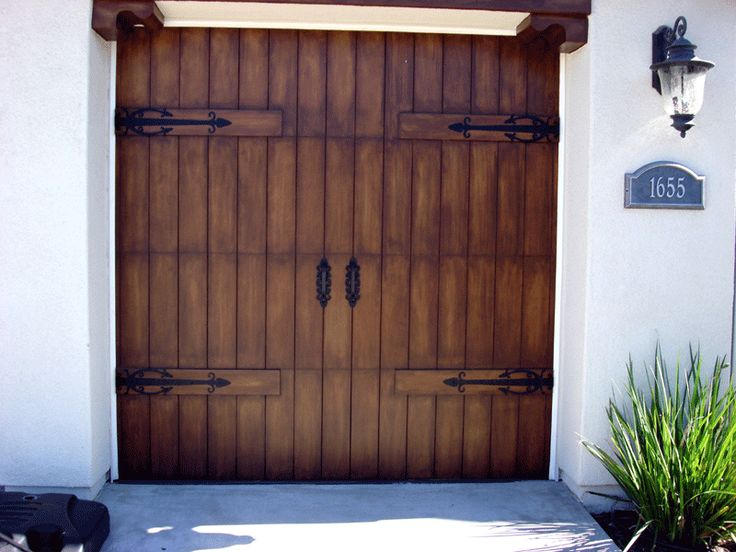 If it's too late or too costly to add real wooden garage doors (five thousand dollars ...each), then maybe this is a second best sollution.  Still add real iron hardware and it's pretty darn convincing even from just a few paces away.