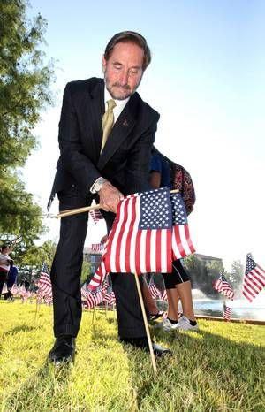 UCO President Don Betz places an American flag near Broncho Lake during a ceremony to commemorate 9-11, Wednesday, September 11, 2013. Students, faculty and staff participated in the remembrance ceremony by placing 2,500 flags around Broncho Lake. Photo by David McDaniel, The Oklahoman