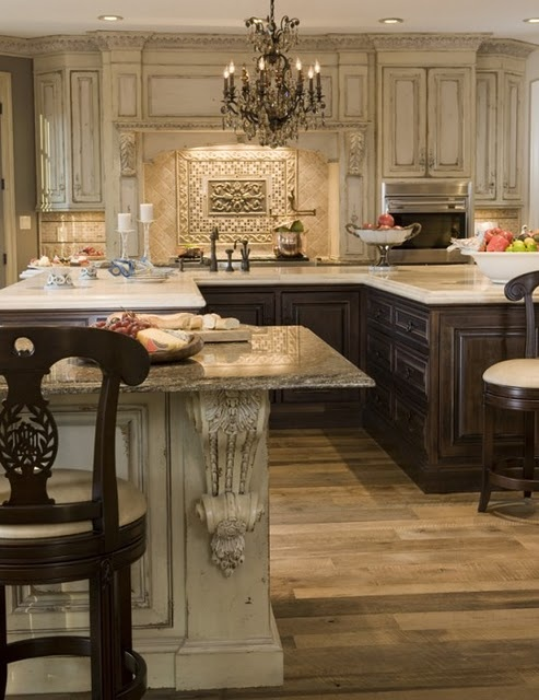 Interesting! Lower cabinets have a dark stain with light marble countertops. Upper cabinets are distressed light color. Adds depth and character to this kitchen.