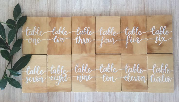 Natural wooden table numbers with white hand written calligraphy. Perfect for a rustic luxe wedding.