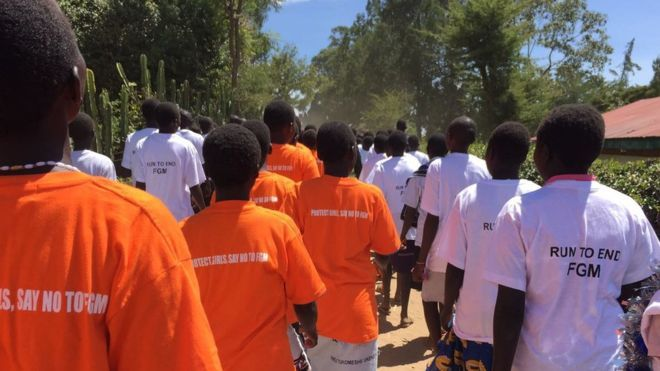 "Students walk in a line wearing orange t-shirts that say ""Protect girls, say no to FGM"" and white t-shirts saying: Run To end FGM"