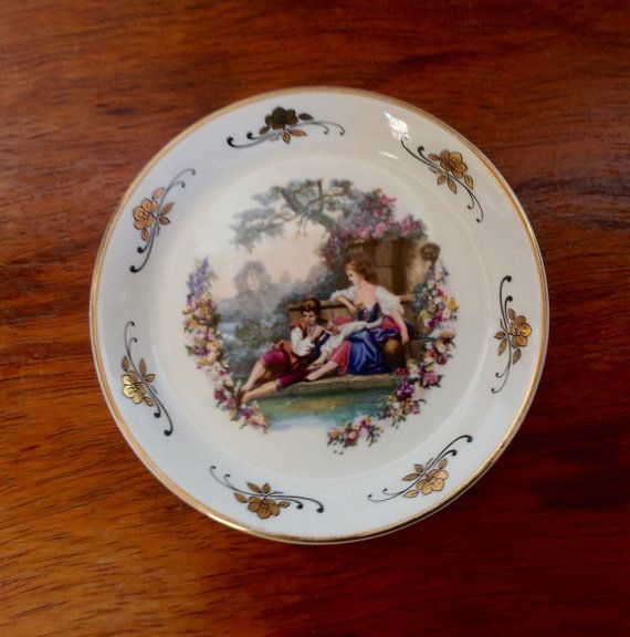 A beautifully decorated Lord Nelson Pottery pin dish, made in England in the 1970s. Dish measures 4.5 across, 1.7 tall, and depicts an 18th Century couple with gold flowers and edging.  In good condition, a lovely piece for a dressing table or display cabinet. Please note: We are happy to post our vintage items anywhere in the world. As they would be sent tracked and signed for, we need an address to generate a postage quote. If you would like to order from outside the UK, please message us…
