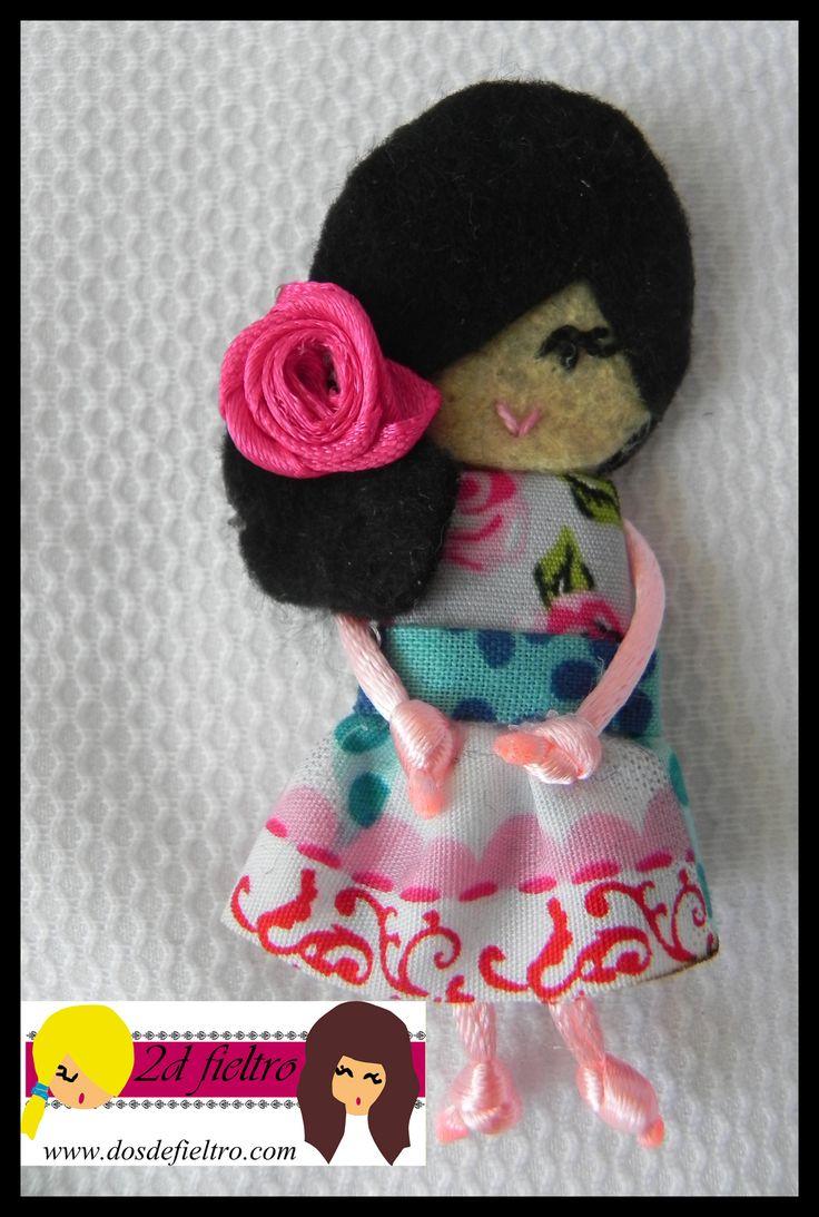muñeca de fieltro morena con flor fucsia en el pelo. Vestido con puntos y flores en tonos azules y rosas.