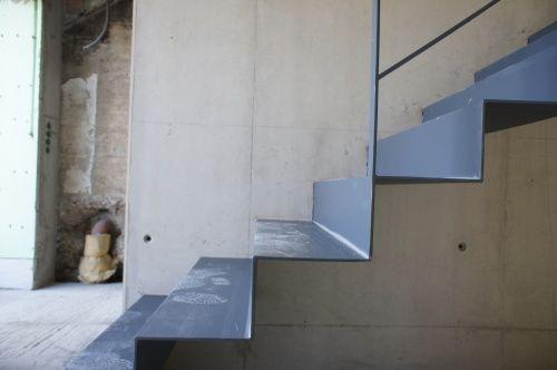 Gefaltete Blechtreppe, eingespannt in eine Sichtbetonwand