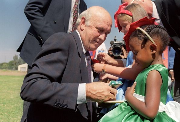 South African President Frederik Willem de Klerk admires a gift from a young Nationalist Party supporter at his election rally in Smithfield southern...