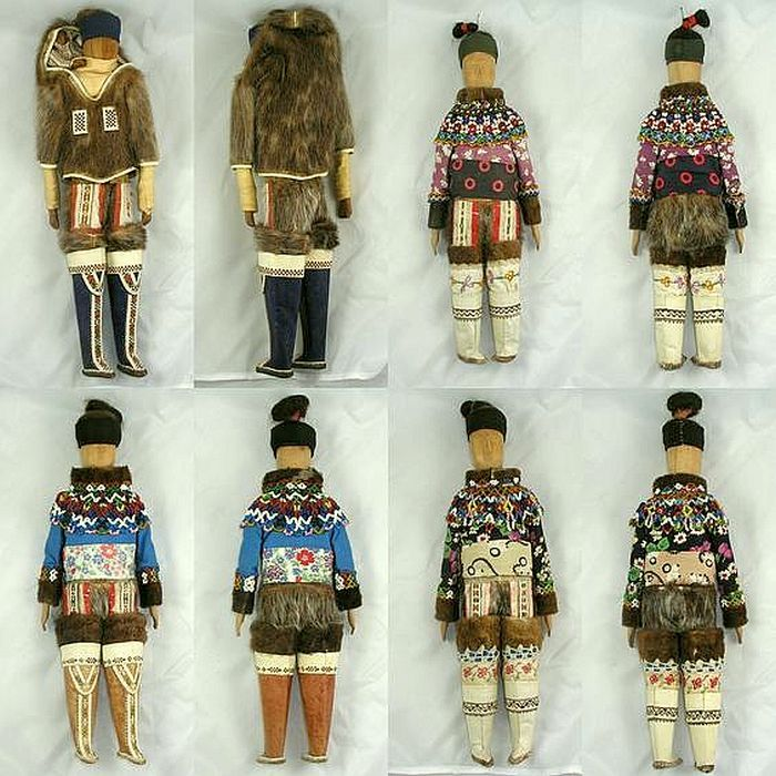 A set of four carved wooden Greenland Eskimo dolls, c. 1900-1910. Three women in summer outfits (all different), and one woman in winter gear with a carved baby on her back.