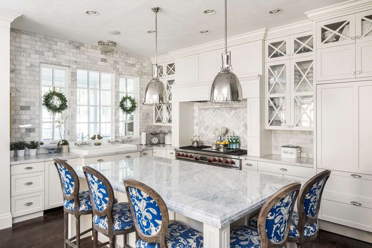 Classic white kitchen with blue dining chairs around central island. Design by The Fox Group. #classickitchen #whitekitchen #blueandwhite #interiordesigninspiration