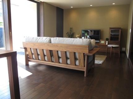 ダーク色の床にウォールナット無垢材の家具でコーディネートした実例です。背面が美しいウッドフレームソファ「Reck」