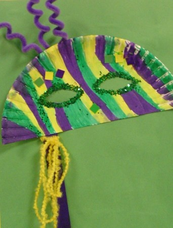 Cut a Paper Plate in half.Finally,to get your Mask put Glitter,Paint,Yarn,and Pipe Cleaners to decorate.