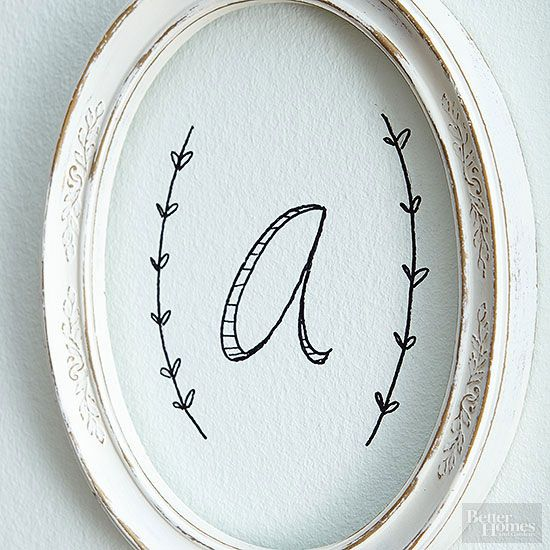 Create a whimsical monogram drawing with just colored paper and a black marker. Freehand a letter surrounded by two twigs. We bordered this versionwith a rustic oval frame, perfect for adding interest to a gallery wall./