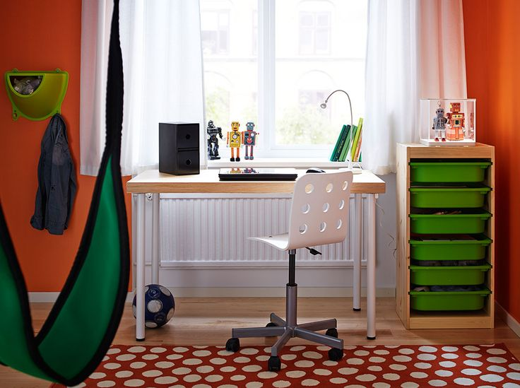 A children's room with a desk in pine with white legs, a white chair and storage in pine with green plastic boxes