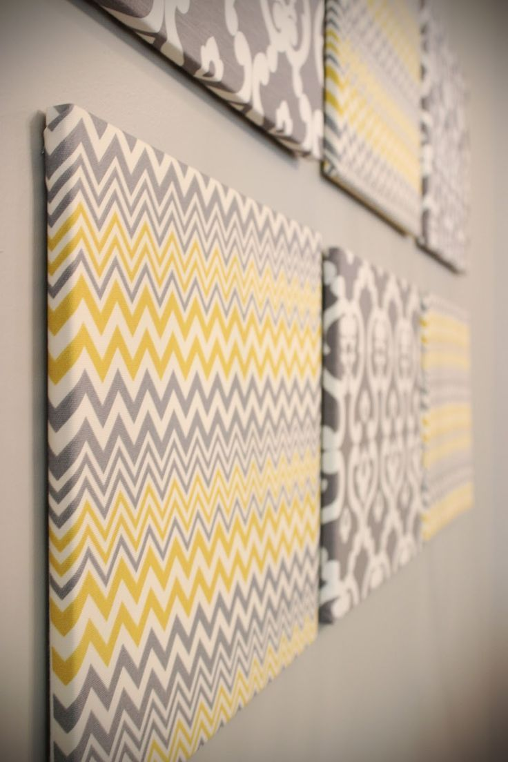 Blank canvases with cute fabric stapled over them. Perfect for a yellow and gray bathroom.