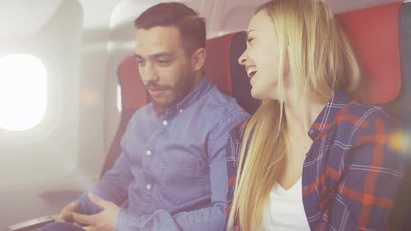 On a Plane Flight Handsome Hispanic Man Tells Funny Story to His Beautiful Blonde Girlfriend