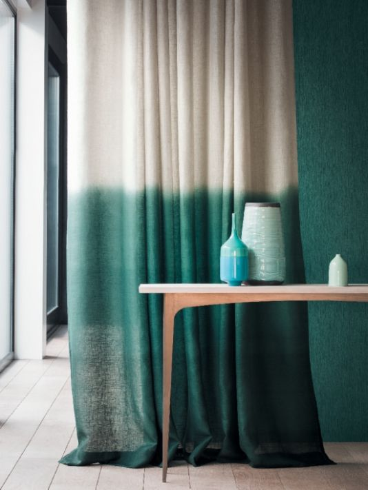 Breva Sheer Fabric An ethereal wide width sheer linen fabric dyed to create an ombre effect. Shown in forest green and natural linen. This design is railroaded.