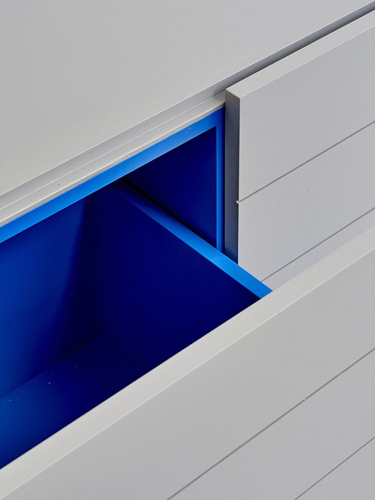 Grey cabinetry with inside drawers painted in Klein blue custom designed by Fiona Lynch Design.