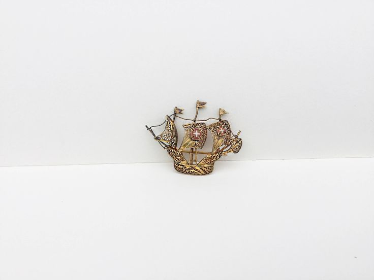 Fantastic little gold tone filigree ship brooch with two little Swiss flags (may not be, may be Spanish galleon?) gorgeous detail, the brooch dates back to 1920, it's in good antique condition. The making of filigree metal takes a lot of skill, these brooches would take weeks, so,sties even mo