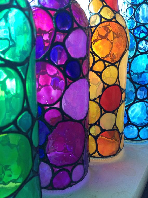 Este es un lindo conjunto de 4 botellas de cerveza recicladas. Tengo mano pintado con colores de la ventana para darles un aspecto de vidrieras. Ellos se ven increíbles en la luz del sol, pero quedaría sólo como lindos en un estante en algún lugar de tu casa.    Estos no pretenden estar afuera. Pueden limpiarse con un paño húmedo.