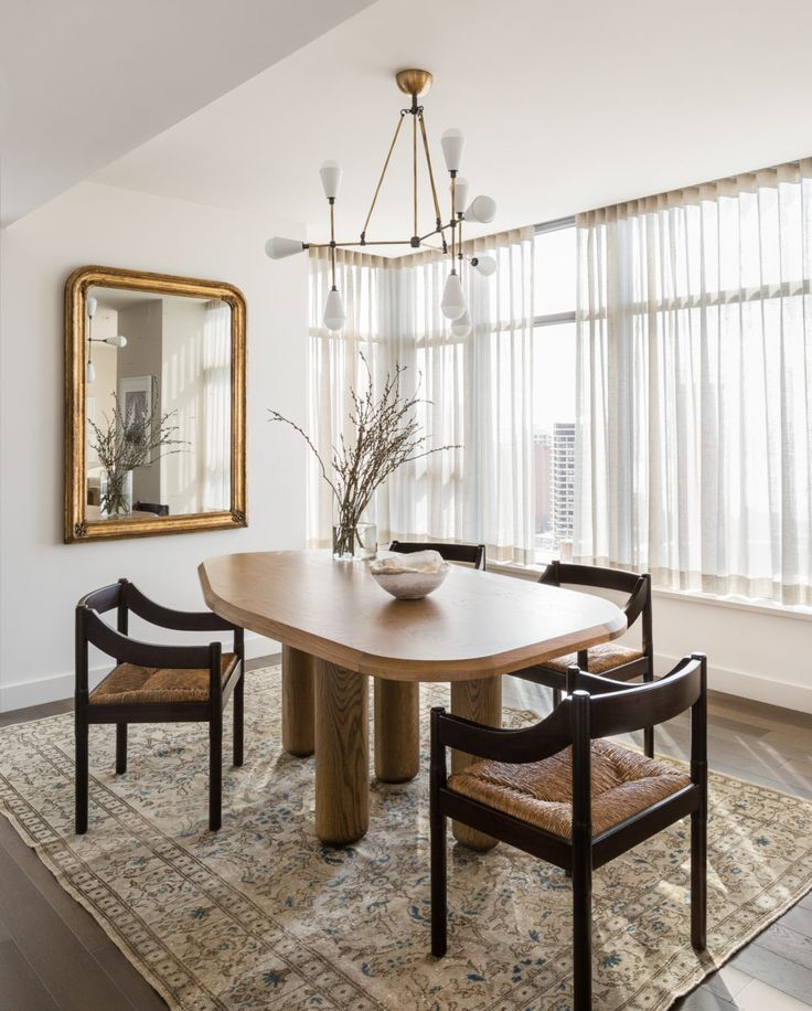 Transitional dining room withmodern chandelier brass mirror