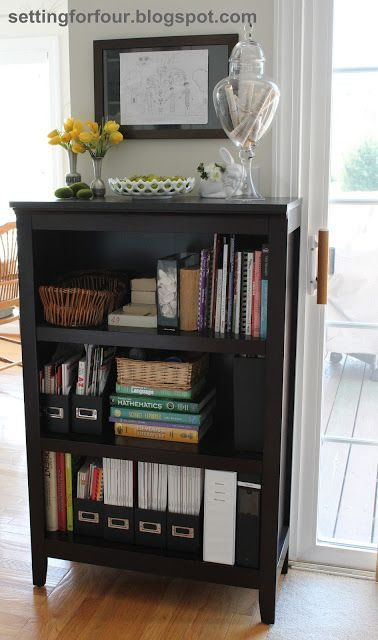 Bookcase Family Organizer: This bookcase is the hub of our home for organizing homework, cookbooks, and kid's stuff to keep handy in one place. It's located in between our kitchen and family room in our open concept home, in a central location that is passed by everyone in our family through the day. Check out all the ways I organized our family here!