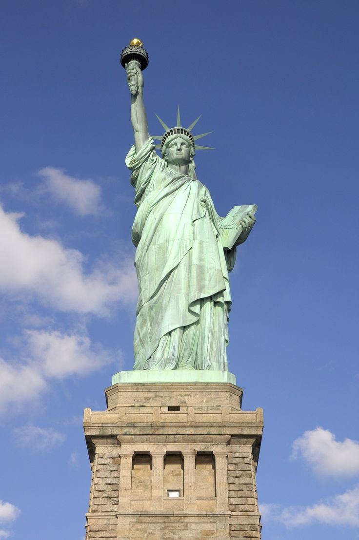 """A gift to the U.S. from France, the Statue of Liberty was erected off the southern tip of Manhattan in 1886. From the ground to the tip of her torch, Lady Liberty stands just over 300 feet tall. Designed by Frédéric Auguste Bartholdi, the statue has a crown of seven rays, representing the seven seas and continents, and a tablet inscribed with """"July IV MDCCLXXVI,"""" celebrating the date the U.S. declared independence from British."""