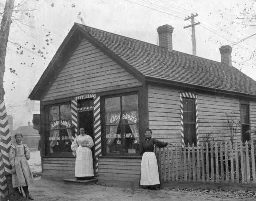 """View of a barber shop on 4th (Fourth) Avenue, in Denver, Colorado; shows women posing by a house with stripes and window letters: """"Lady Barber Haircutting Shaving."""" 1902"""
