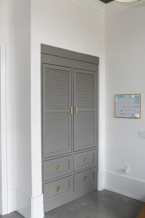 Charcoal gray laundry room features charcoal gray louvered cabinets adorned with brass handles built above stacked gray drawers adorned with vintage brass ring hardware situated next to a dry erase calendar board.