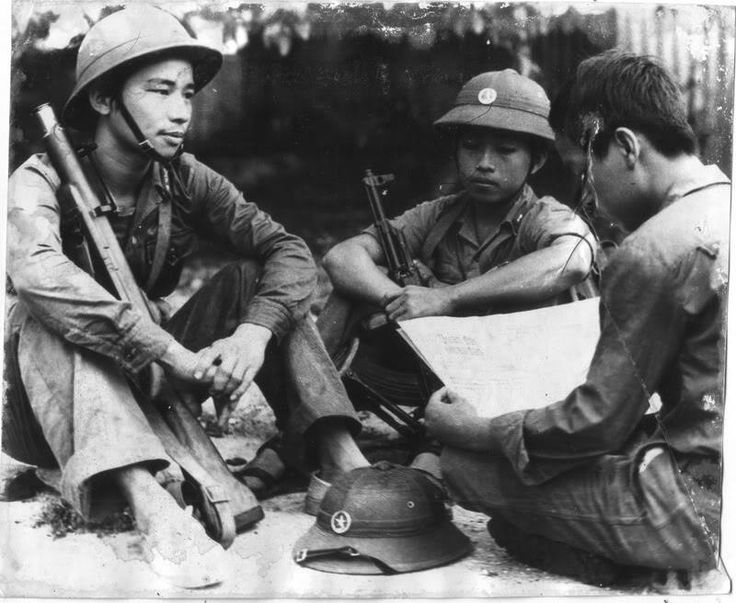 North Vietnamese Armu soldiers sit in a circle. One of them is armed with a Type 56 assault rifle while the other has a captured M79 grenade launcher. The standard NVA pith helmet is visible on the ground.