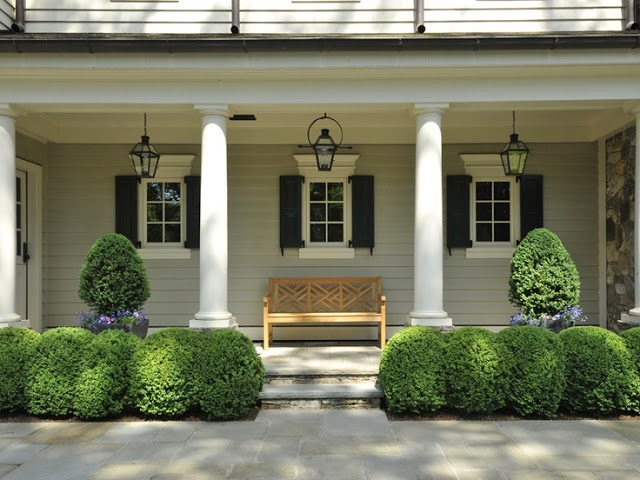 side porch with lanterns and boxwoods