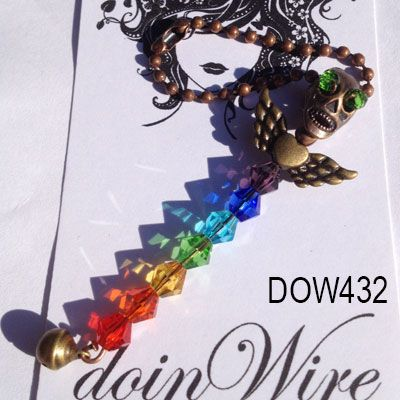 doinWire-Pendant, Antique brass tone skull with green crystal eyes, antique brass tone heart/wings body, chakra crystals, brass tone bell on copper tone ball chain necklace.