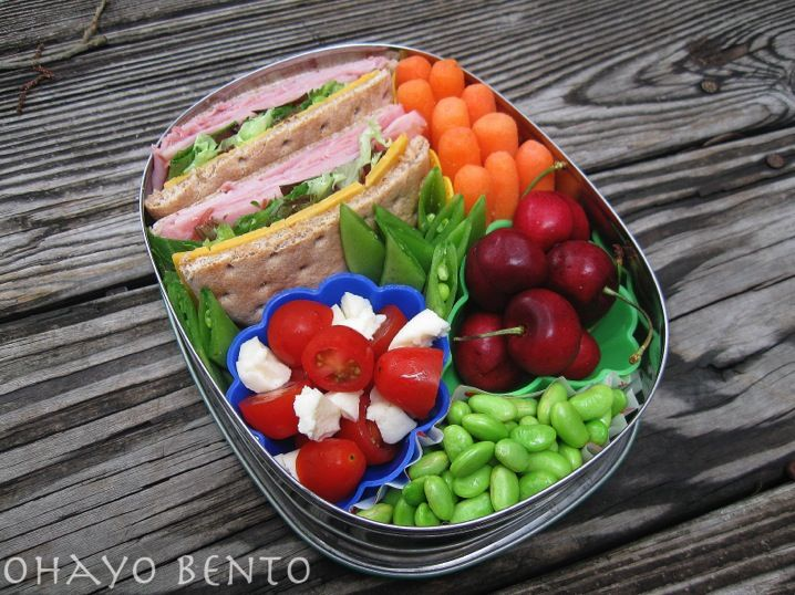 ham, cheddar, and greens sandwich, tomato and cheese salad, soy beans, cherries, raw sugar snaps, and carrot sticks.