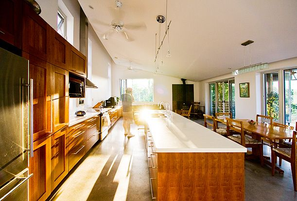 Gananoque Lake Road House - The great room features a large kitchen, dining and living spaces with a polished concrete floor.  In the back corner a wood stove brings warm and cheer to the room on cold winter nights.