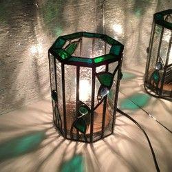 ステンドグラスの技法で制作しています。流れるツタの葉っぱに 雫をイメージしたビー玉を施した 8面体のテーブルランプです。放射線状に伸びるヒカリがとても美しい作品になりました。玄関先や寝室など場所を選ばず飾って頂けるサイズになっております。瑞々しい雰囲気を 是非お楽しみください。手作りの木製配線台、電球込みの価格です。高さ14㎝ 最大直径10㎝
