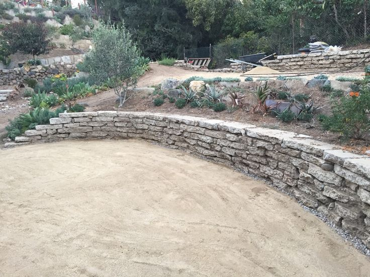 Curved stacked recycled concrete Urbanite retaining walls.