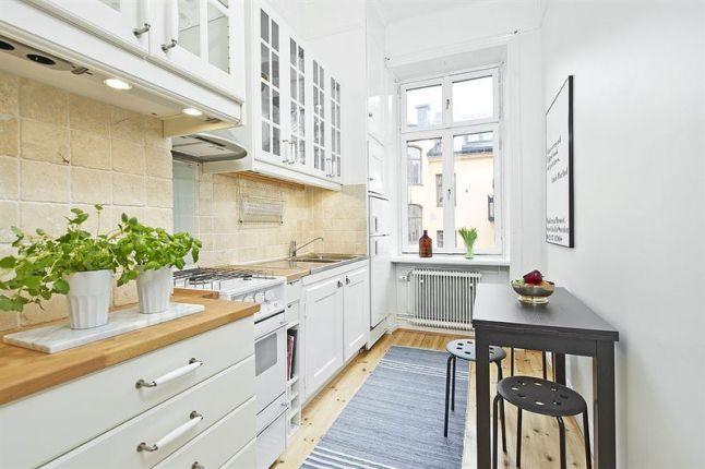 wąska biała kuchnia w stylu skandynawskim z czarnym stołem i metalowymi…