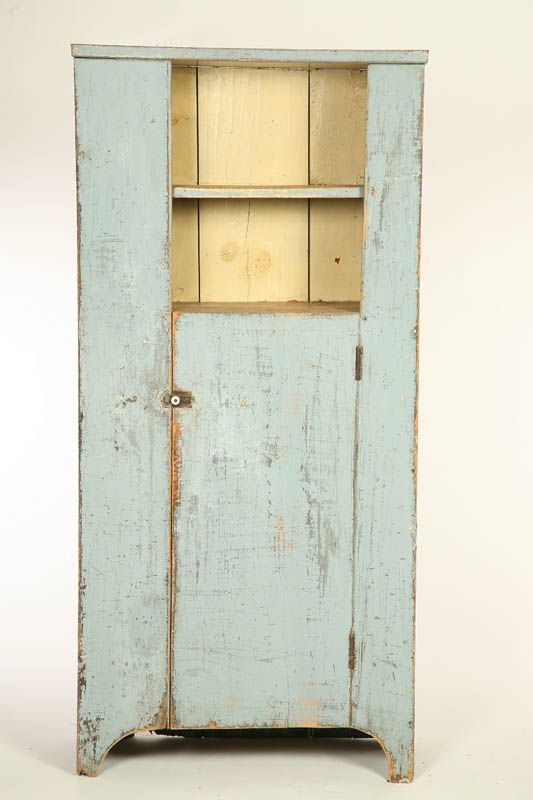 """COUNTRY CUPBOARD.  American, mid 19th century, pine. Old blue paint. Cutout feet, one off center board and batten door, open top shelf and simple board cornice. 65 1/2""""h. 30 1/2""""w. 13 1/4""""d."""
