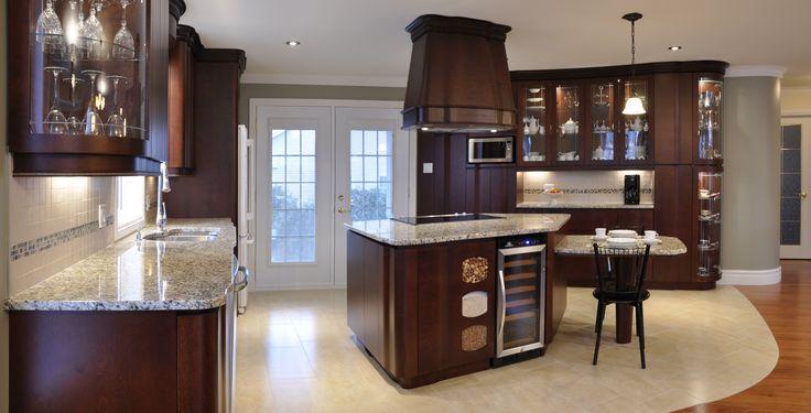 Cette cuisine luxueuse est en merisier teinté, de style moderne au élégantes courbe. Les portes en merisier massif ont été traitées de 2 manières différentes. La section de l'ilot est teinté. La couleur ajoutée aux portes de bois ne masque pas la beauté du grain. Le bois fait directement la couleur ce qui procure aux armoires un effet naturel. Le comptoir de Granit enrichi le style et fait assure l'union de la pierre et du bois donnant un look frais et riche à vos armoires de cuisine.