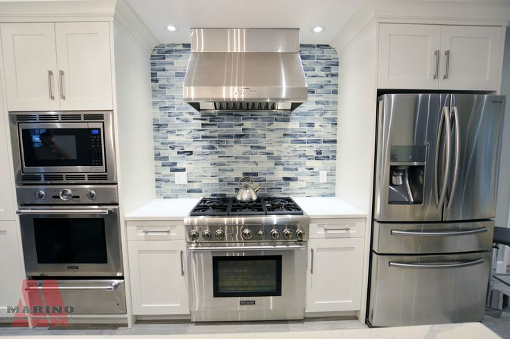 Backsplash in kitchen, stainless steel appliances, and white cabinetry