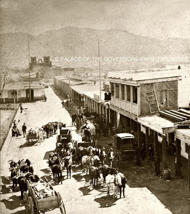 Wagon trains on San Francisco Street at the Plaza in Santa Fe, New Mexico ca. 1869 - 1871. Photograph by Nicholas Brown Nicholas Brown was one of the earliest photographers in New Mexico. Listed as a...