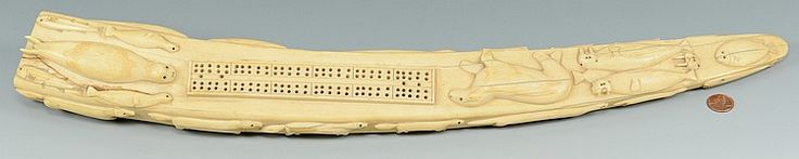 """Large and elaborately carved Inuit or Eskimo walrus ivory tusk, carved in the form of a cribbage board. Decorated with high relief carvings of walruses, fish, seals, wolves, polar bears, dogs and whales throughout with additional red pigment highlights visible around teeth and tusks of animals and scrimshaw detail on fish. 22"""" L. Late 19th century. Provenance: Descendants of the estate of Madge Hardin Walters, early 20th century collector and dealer of Native American"""
