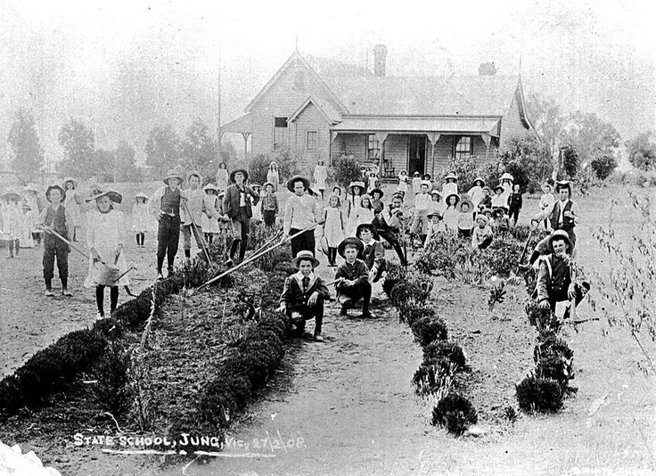 Pupils gardening in the grounds of Jung State School. Many of the children are holding gardening utensils. The weatherboard school is in the background with a residence attached to the side, Feb 1908 - Museum Victoria