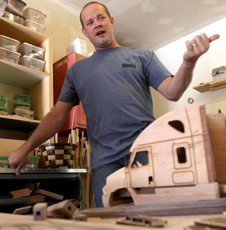 Scott Kidman talks about wood model replicas of Freightliner trucks he has crafted for the NASCAR trucking company. Click through to see more photos. (Photo by John Zsiray)