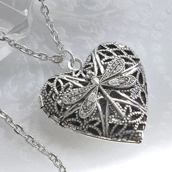 Silver plate heart shaped scent locket with a tiny little silver dragonfly mounted to the top. The pierced open work top has an antique finish,