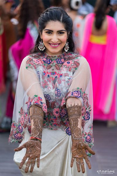 Cape outfit by anamika khanna , dhoti and cape silhouette , offbeat mehendi outfit, white and pink outfit , sheer cape , bride showing off her mehendi , twisty combed back hairstyle , hairstyle for mehendi