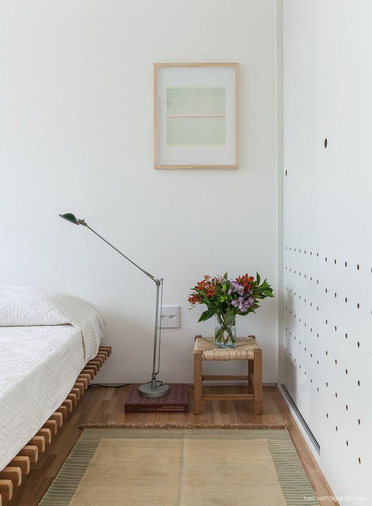 Quarto minimalista tem cama baixa e banquinho com assento de palha usado como criado mudo.