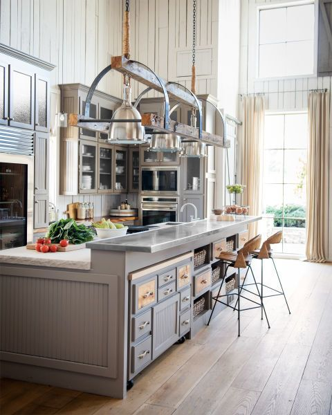 An abundance of moody gray cabinetry, limestone countertops, and stainless steel appliances add luxe elements to the rough-hewn kitchen of country superstar Ronnie Dunn's Tennessee barn home. To maximize storage, one half of the kitchen island contains a series of baskets and bins; the other half has an additional work surface mounted with coasters to roll away when not in use.