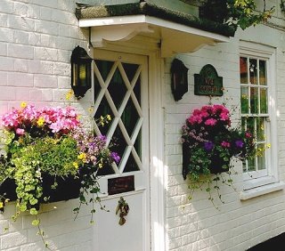 Nice use of flower boxes, lights and other decorative elements to expand the visual size of the front door--very welcoming.