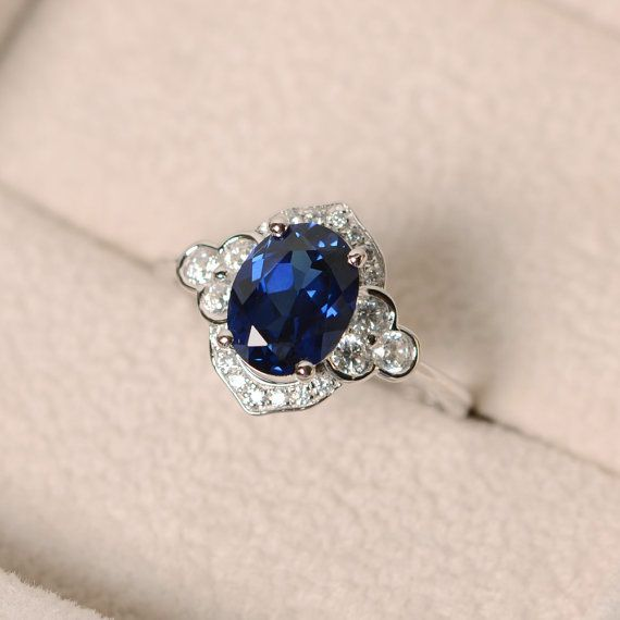 This halo ring features a 7*9mm oval cut lab sapphire and sterling silver finished with rhodium. Customization is available. It is made by hand, and it will take about 7 days to finish the ring after your payment is completed. Any question, just let me know. :)   My shop homepage: https://www.etsy.com/shop/LuoJewelry?ref=l2-shopheader-name