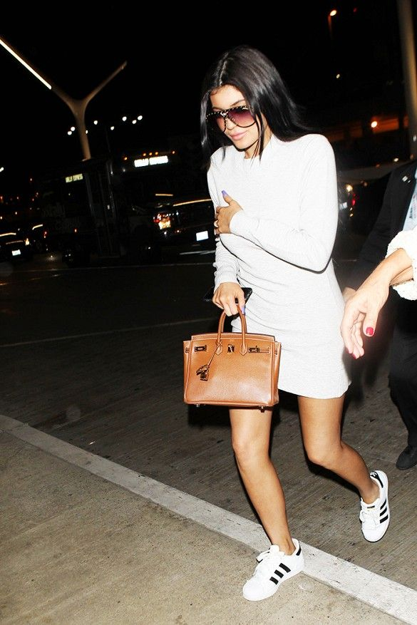 Kylie Jenner wears a white long sleeve cotton dress with sneakers by Adidas, a brown structured mini bag and sunglasses.